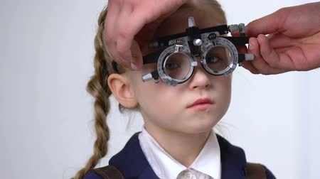 optyk : Male oculist checking schoolgirl vision, smiling kid wearing phoropter, medicine Wideo