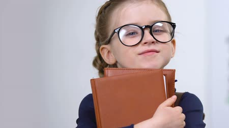 wzrok : Adorable female pupil in eyeglasses holding books, need of knowledge, genius Wideo