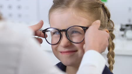 optyk : Ophthalmologist helping small girl to put on eyeglasses, corrective lenses