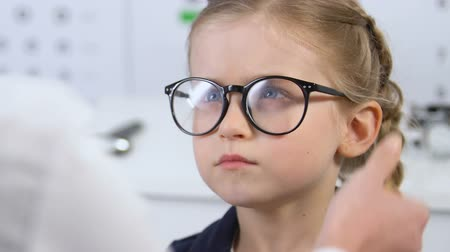 nearsightedness : Sad female kid wearing eyeglasses prescribed doctor, child insecurities, frame