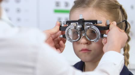 phoropter : Optometrist examining girl eyesight using optical trial frame, vision checkup