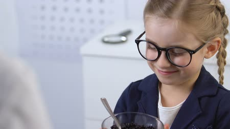 çinko : Female oculist giving blueberry bowl to kid in eyeglasses, eye health, vitamins Stok Video