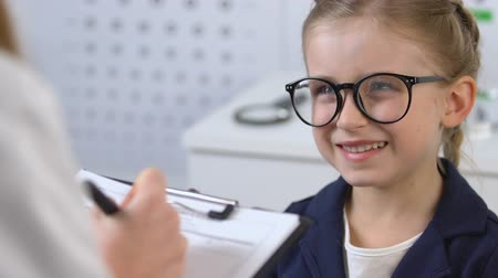 prescribe : Smiling schoolgirl in eyeglasses looking at ophthalmologist writing prescription