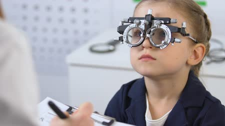 prescribe : Kid in optical trial frame looking doctor prescribing eyeglasses, ophthalmology