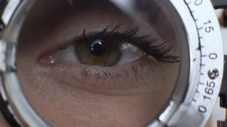 phoropter : Woman looking through phoropter choosing proper lens, ophthalmologic clinic Stock Footage