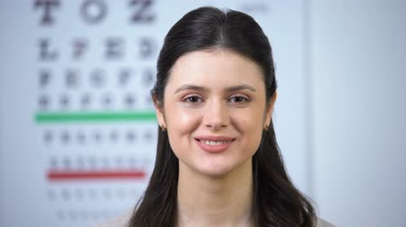 wizja : Attractive lady smiling to camera during visit to optometrist, eyesight checkup Wideo