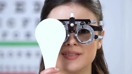 phoropter : Smiling woman in phoropter closing one eye, vision examination, health check