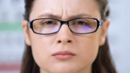 blindness : Female looking through glasses with partly closed eyes, vision disorder, problem