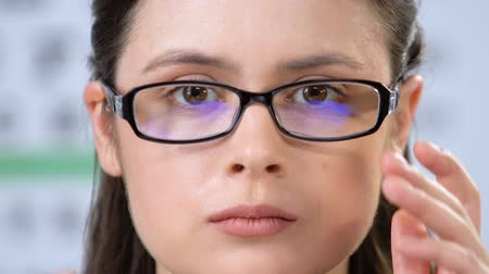 optique : Sad woman with vision disorder fitting eyeglasses, health problems, insecurity Vidéos Libres De Droits