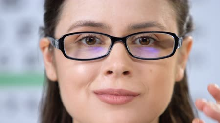 myopie : Female with blurred vision fitting eye glasses and smiling at camera, health