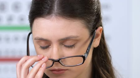 мигрень : Exhausted woman taking off eye glasses and massaging nose, improper lens