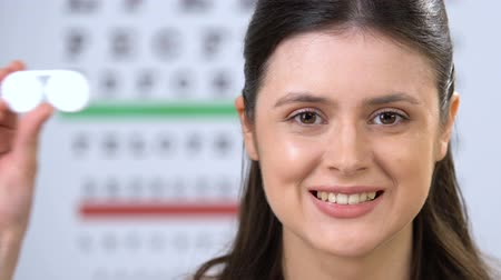 miopia : Smiling female showing contact lens at camera, patient recommendation, choice Filmati Stock