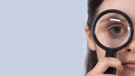 wzrok : Curious female looking through magnifying glass, studying information, survey Wideo