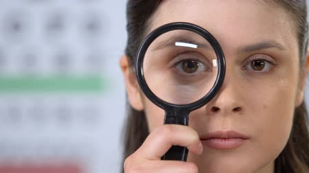 astigmatism : Female looking through magnifying glass, trying to concentrate, vision check