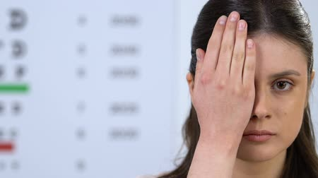 refractive : Woman closing eye with hand, checking vision on ophthalmology appointment