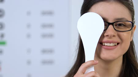 refractive : Happy woman in eyeglasses closing one eye, vision checking device, healthcare Stock Footage
