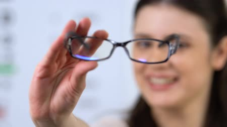 optyk : Cheerful woman proposing eyeglasses, patient recommendation, vision support