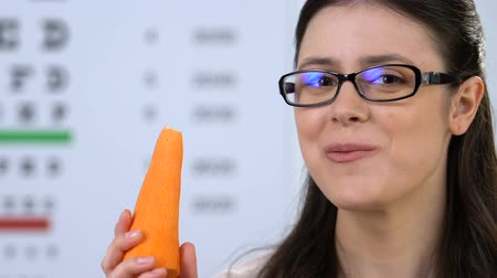 rekomendacja : Happy female in eyeglasses eating carrot, fresh vitamins for eyes care, carotene