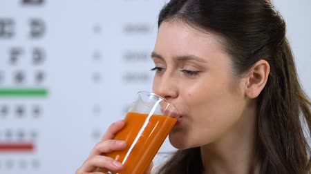 ajánlás : Female drinking delicious carrot juice, supplement for vision health, nutrition