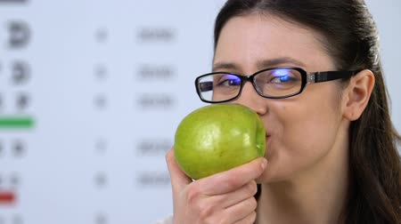 ajánlás : Cheerful woman in eyeglasses eating green apple, health dieting, vitamins Stock mozgókép