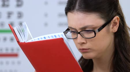 grãos : Concentrated female student in eyeglasses reading book, university education