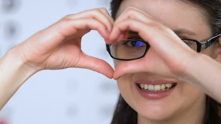 refractive : Female in glasses showing heart sign with hands, vision health care, clinic