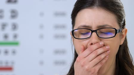 refractive : Woman in eyeglasses yawning on ophthalmologic examination, doctor check-up