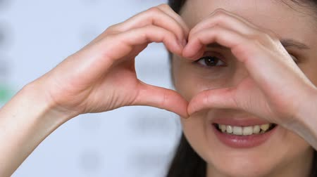 refractive : Smiling female looking through heart sign made with hands, charity concept Stock Footage