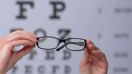 refractive : Person holding eyeglasses against eyechart, vision disorder prevention, clinic Stock Footage