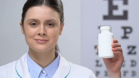 ajánlás : Female doctor holding pills bottle against eye chart background, ophthalmology