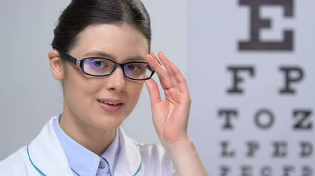 amblyopia : Professional female optician looking at camera against eye chart background Stock Footage