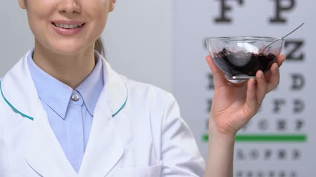 scheel : Female doctor showing bilberry at camera against eye chart, vision health care