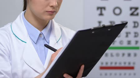 zabránit : Cheerful female ophthalmologist filling patient examination data, diagnosis