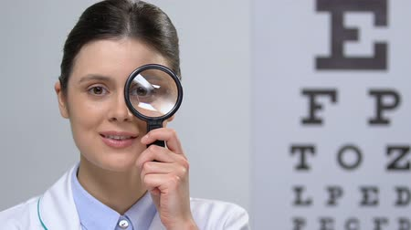 amblyopia : Smiling nurse looking at camera through magnifying glass, health check, vision