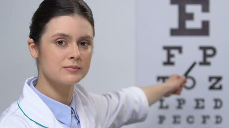 amblyopia : Female ophthalmologist showing letters on eye chart, vision examination, clinic Stock Footage