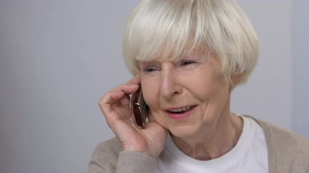 parentes : Smiling senior woman talking phone, family care, happy relationship, close-up Stock Footage