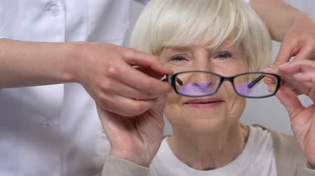 refractive : Doctor giving eyeglasses to happy elderly woman with vision problems, health