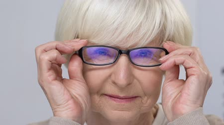 refractive : Smiling senior woman fitting eyeglasses, elderly customer in optical store