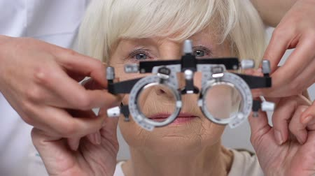 blindness : Ophthalmologist putting phoropter on elderly woman eyes, vision examination