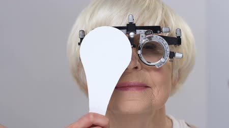 closing : Smiling elderly woman wearing phoropter closing one eye, vision examination Stock Footage