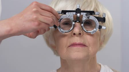 refractive : Optician fixing lens in phoropter wearing senior female patient, vision problem