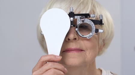 health insurance : Smiling senior woman wearing phoropter closing one eye, good vision, testing
