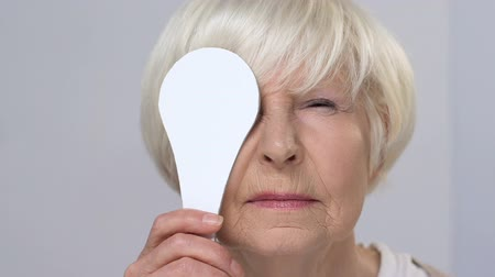 blindness : Smiling elderly female squinting on vision examination, closing one eye, health