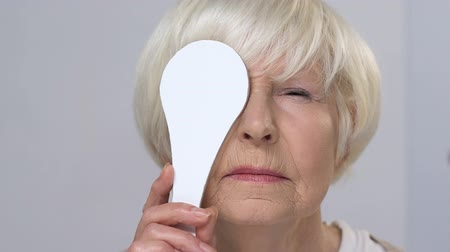 refractive : Upset elderly woman squinting eyes on ophthalmological examination, disorder
