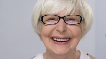 plezant : Elderly lady in eye glasses happily smiling at camera, health care, examination