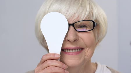refractive : Smiling aged woman in eyeglasses closing one eye, checking vision in clinic