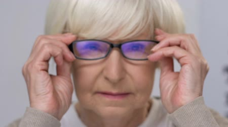 refractive : Elderly lady wearing eye glasses cheerfully smiling at camera, vision care Stock Footage