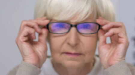 errado : Senior woman fitting eye glasses, incorrect optical device, vision problems