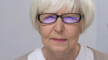 refractive : Upset elderly female focusing vision through eye glasses, health problem, clinic Stock Footage