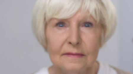 refractive : Elderly woman looking with partly closing eyes, focusing vision, health problem